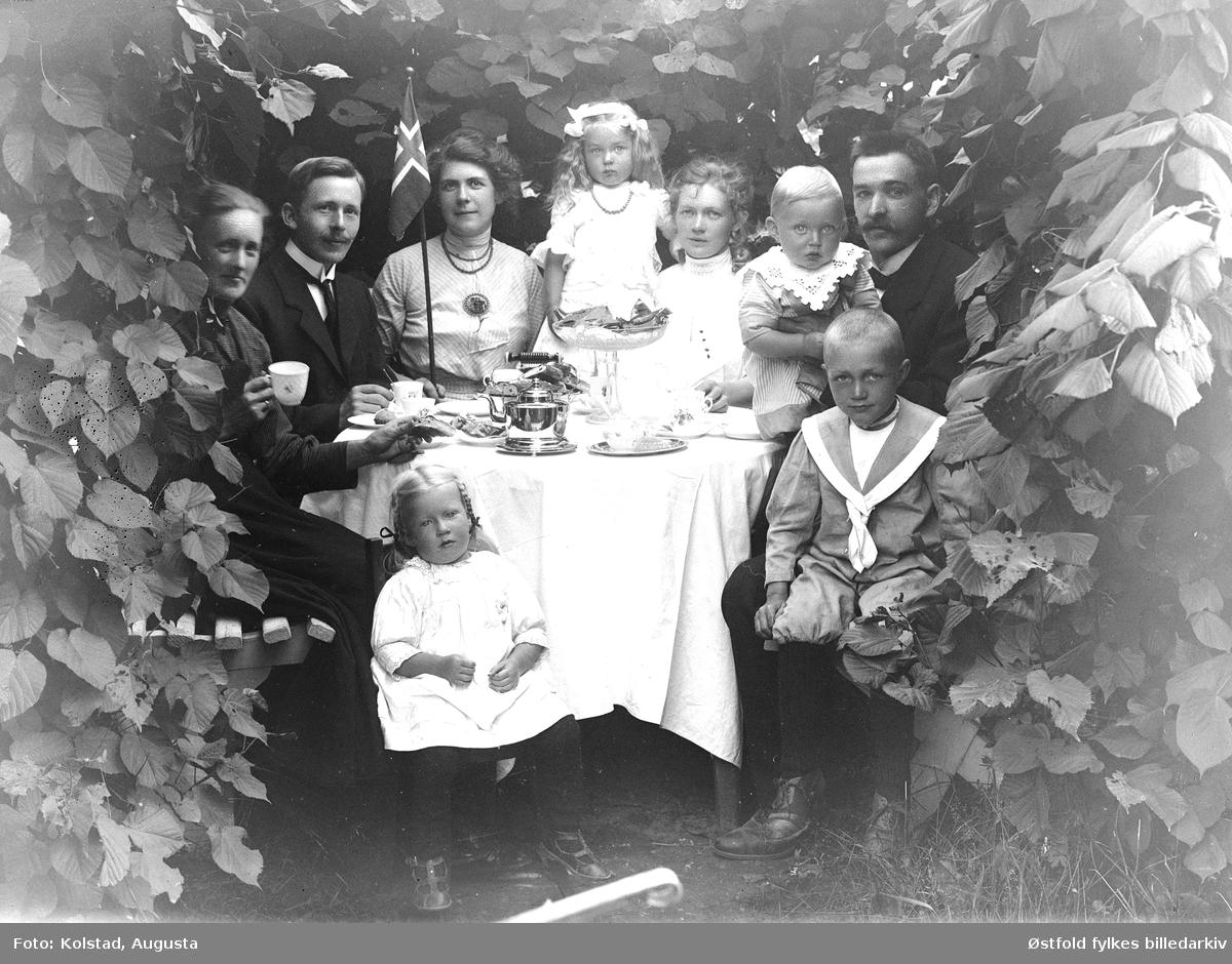 Kaffeslabberas utendørs i hagen, med ukjent familiegruppe rundt bordet.
