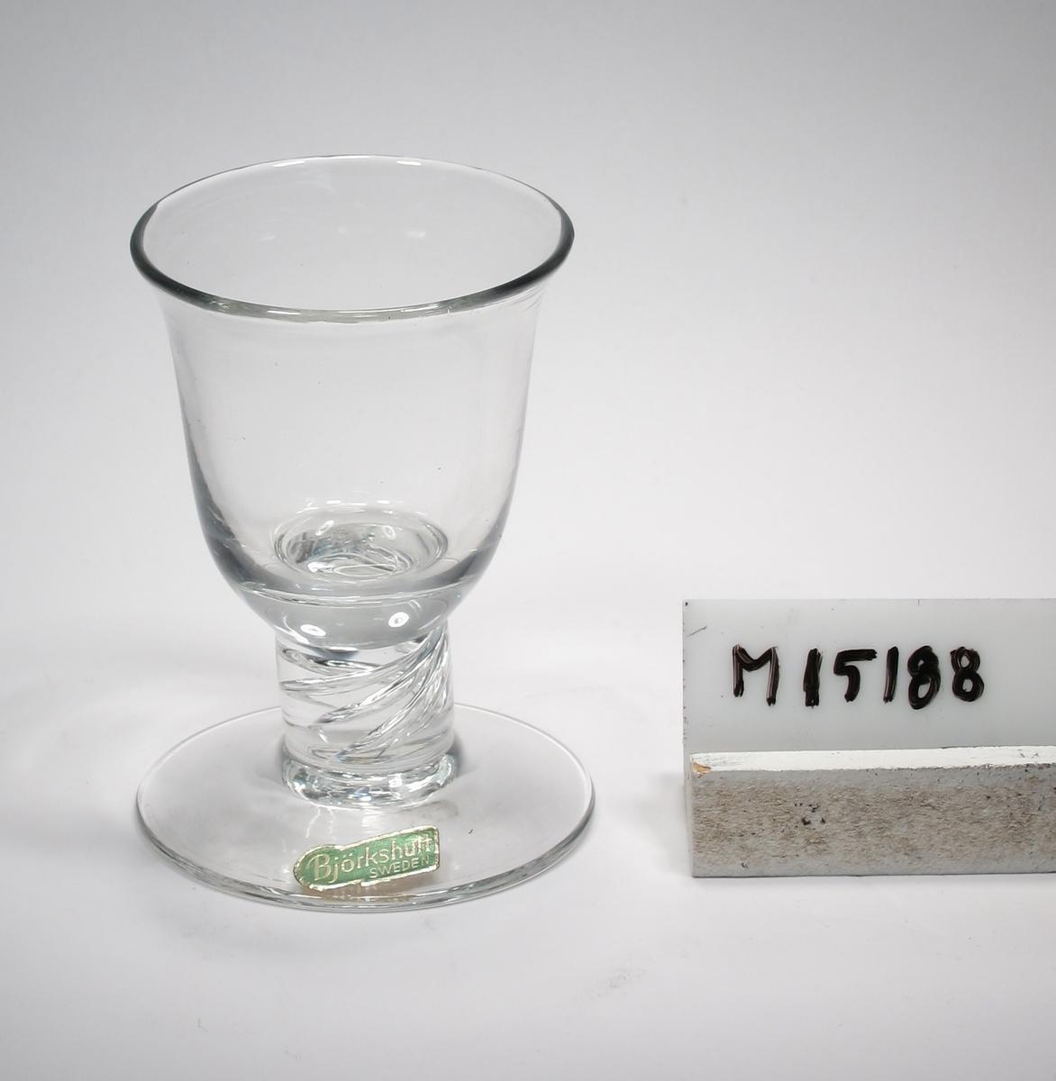 """Glas. Klockformad kuppa. Kort, rakt ben, skivfot. I benet luft i spiralslingor. Ofärgat klarglas. Ovan angivna mått avser mynningens diameter. Fotdiameter: 64 mm. Avlång, grön etikett med text. Se """"Signering, märkning"""" ovan. Inskrivet i huvudkatalogen 1952. Funktion: Glas"""