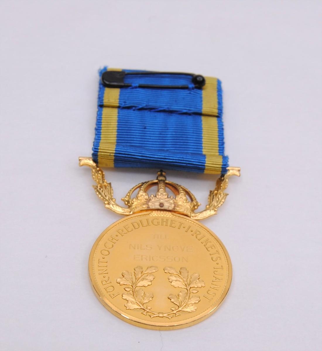 """En rund präglad medalj av 23K guld """"för nit och redlighet i rikets tjänst"""". Motiv av Gustaf VI Adolfs huvud på ena sidan samt text. På den andra sidan två eklöv samt gravyr. På sidan av myntet sitter tre stämplar. Medaljen är krönt av en krona med bladverk på sidorna som går upp i fäste för tygband. Tygbandet är blått med två gula ränder. En säkerhetsnål är fäst på baksidan av bandet.(:1)  Etui av papp klätt med präglat papper. Inredning av grön sammet och vitt siden. Text tryckt i locket.(:2)"""