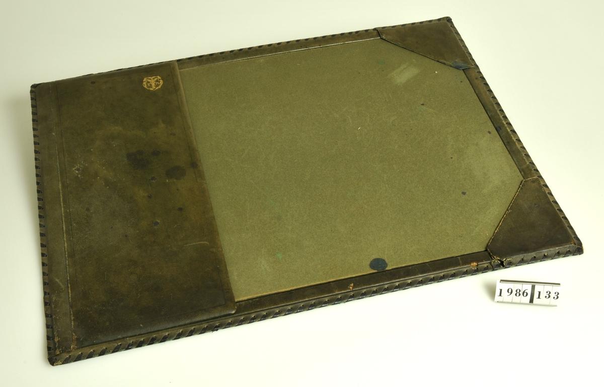 Grön. Klaff med vapen i guld med initialerna TMB. Laskade kanter. Baksidan klädd med filt. Läskpapper. Kalender från 1940.