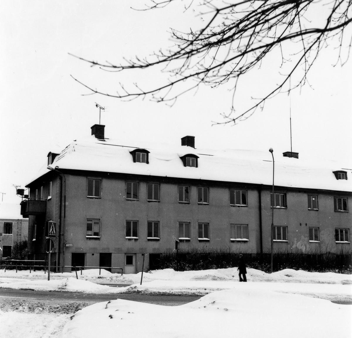 Vinterbild korsningen Kungsgatan och Vänersborgsvägen med ett 2 vånings bostadshus i centrum på bild.  Bostadshus i två våningar med butikslokaler i källarplan utmed Kungsgatan. Entrépartier mot gårdssidan. Putsade väggar, tvåkupigt taktegel. Lägenheter försedda med kakelugn i ett rum. Parkettgolv. Beslut om rivning i november 1978. Fastighetägare: Alingsås kommun.