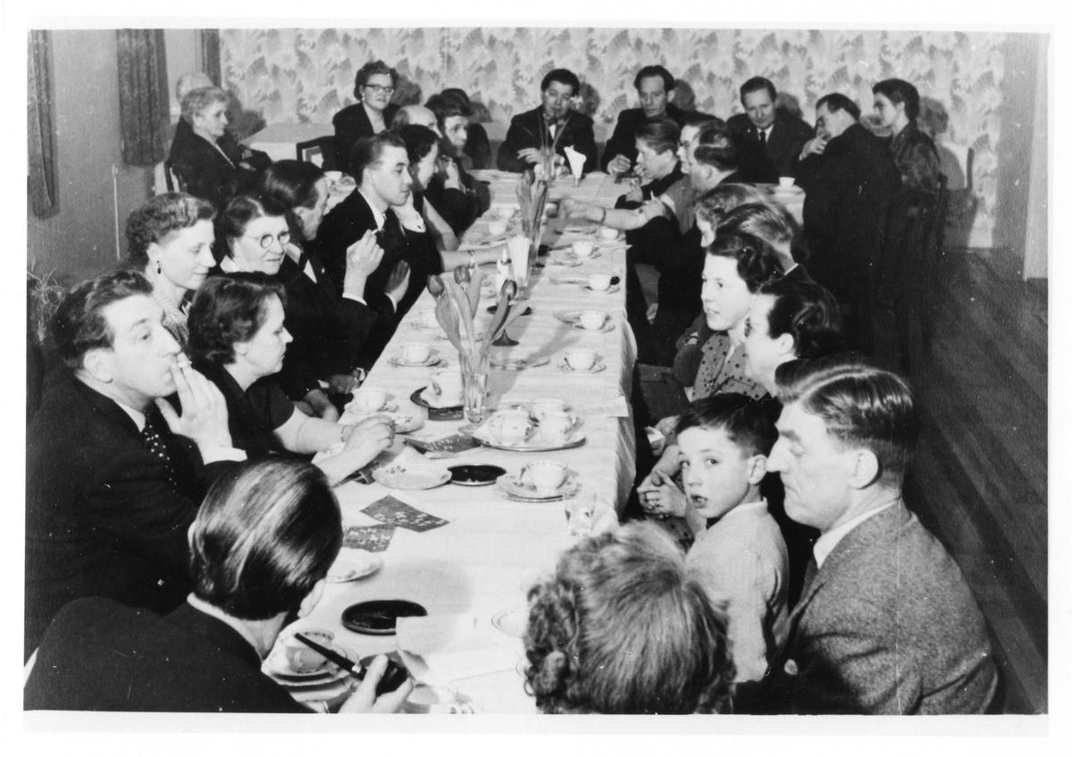 Ett 30-tal kvinnor och män samlade kring ett långbord, dukat med kaffeporslin och blomvaser. På bilden syns Folket-i-Bilds ombud, Filip Wingqvist, distriktsombud. Håkan Johansson, centralombud, Alingsås sitter i mitten av de tre mä)nen längst bak.