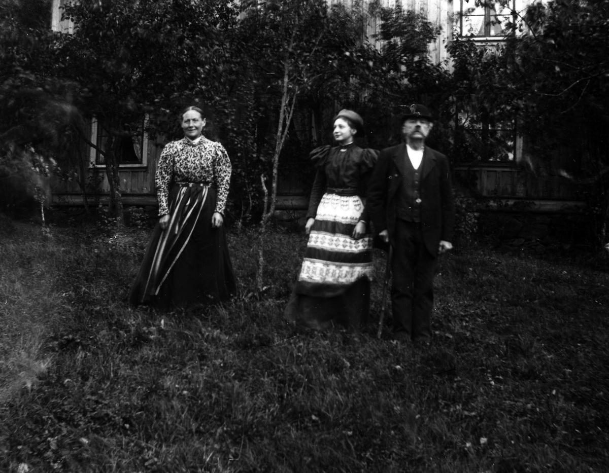 Gruppbild på två kvinnor och en man i en trädgård.