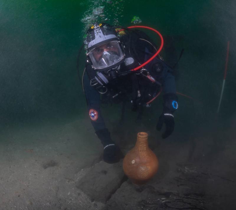 Dykkende arkeolog viser frem bartmannskrukke funnet i vraket av det som antas å være Pelikanen. (Foto/Photo)