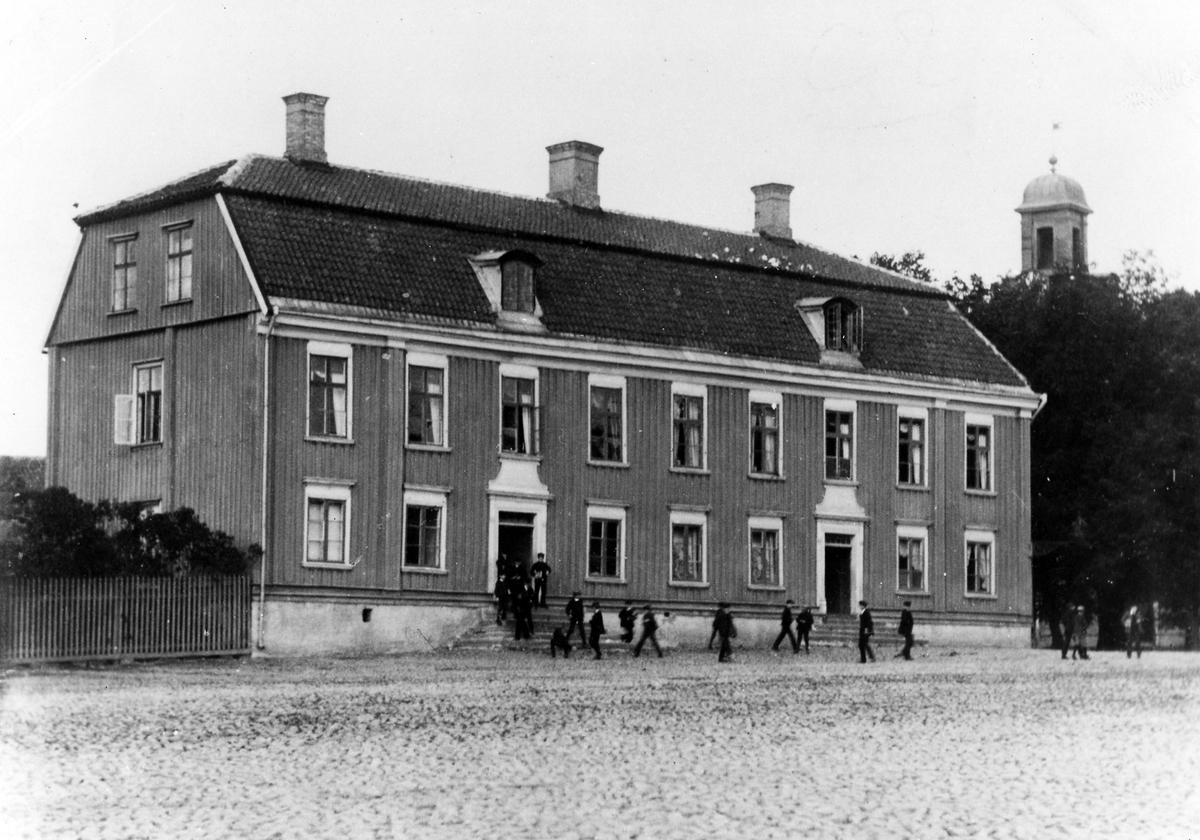 Rådhuset där läroverket var inrymt vid sekelskiftet. En stor grupp barn syns utanför byggnaden.