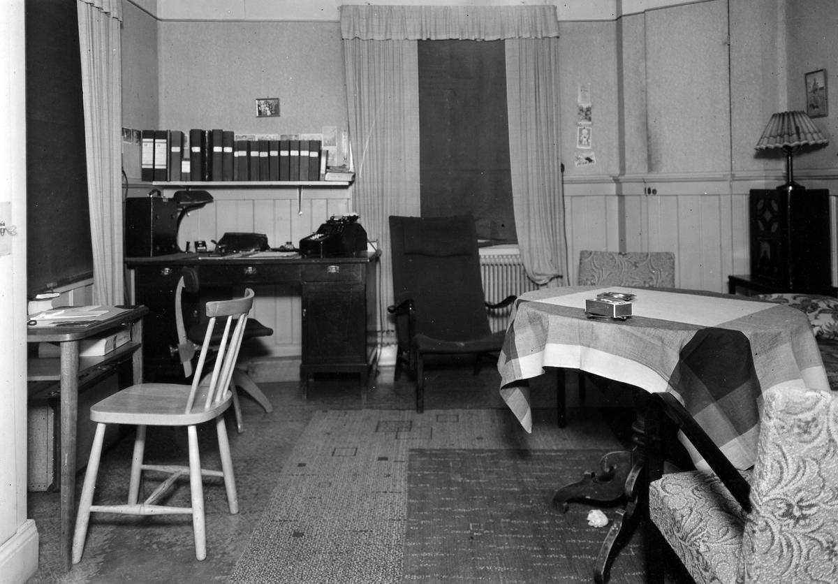 Vaktrummet på apoteket Hjorten. Bilden visar ett rum med bland annat två skrivbord, hylla med pärmar, bord och fåtöljer.