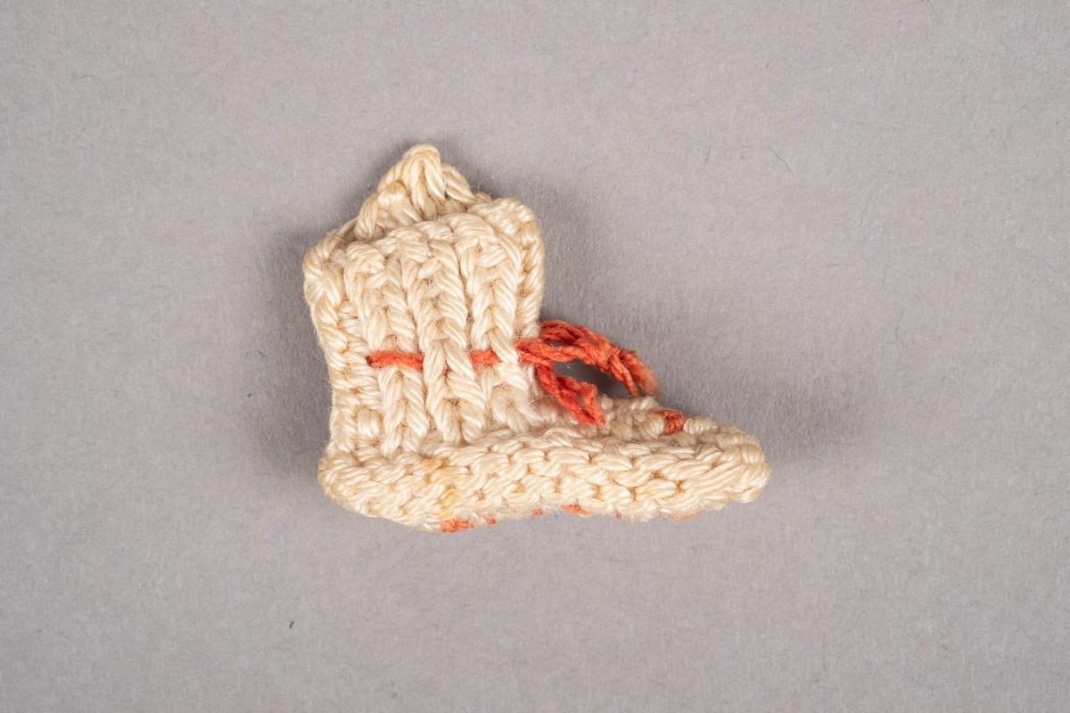 """Strikket miniatyrsokk. Sokken er strikket med hvitt garn. Den har rosa snøring. Det er brodert """"Grini"""" på undersiden."""