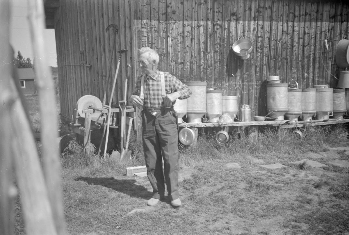 Ole Kolrud på Veslesætra med melkespann, slipestein og diverse redskap