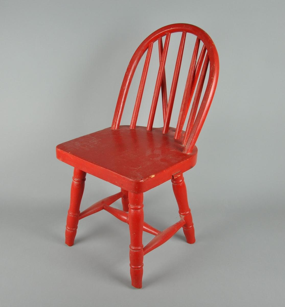 Rødmalt barnestol av tre. Stolen er formet som en budalsstol.