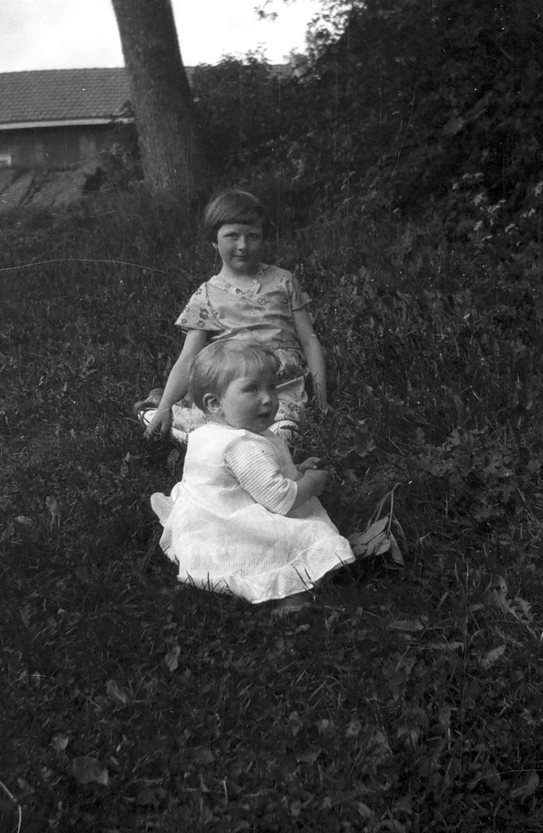 To småjenter på grasbakke.