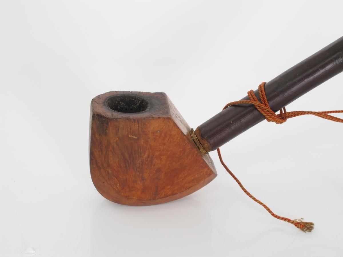 Langpipe.   Bruyérerot (knuteformete utvekster på rot som brukes til å lage pipehoder, mye kiselsyre gjør at treverket brenner dårlig)., Skaft av mørk never. Sort hestehårssnor med ibenholtledd i begge  ender av snoren. Stort pipehode, øvre del vinkelformt, nedre del rundet profil, tresidet.  Forholdsvis tykt neverskaft, lett buet  øvre del, tynn rød snor.