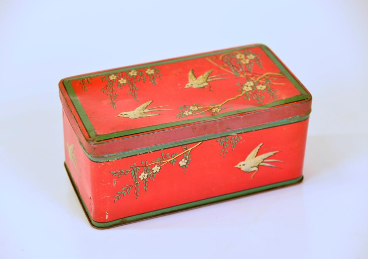 Dekor i rött, vitt, grönt och guld med blommande bladrika grenar och småfåglar.   Från Arne Ekströms handelsmuseum.