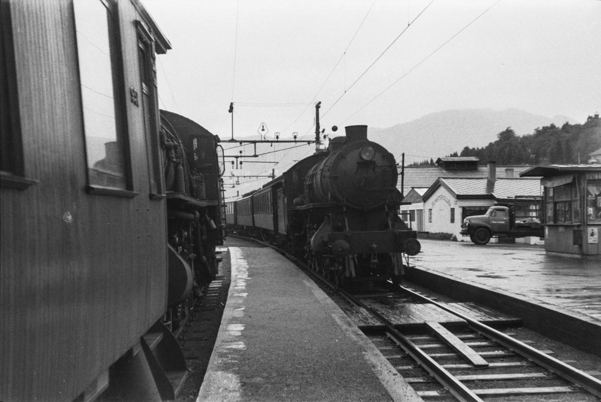 Kryssing på Minde stasjon. Begge togene trekkes av damplokomotiv type 31a.