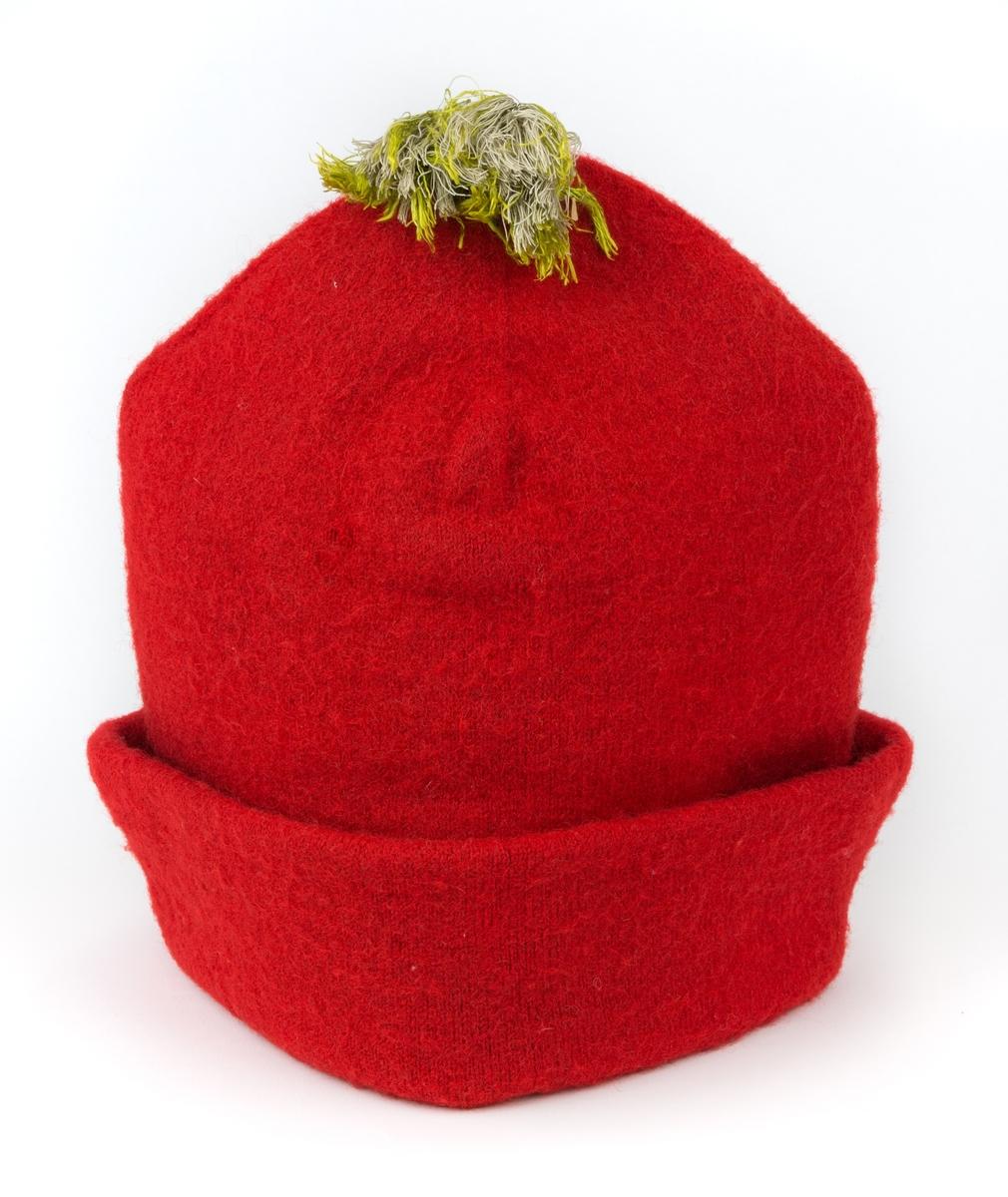 """Mansluva, så kallad """"rödluva"""", stickad av rött ullgarn, dubbel. Filtad och fodrad med linnelärft. Grön silkestofs."""