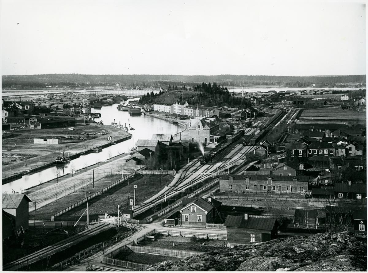 Utsikt över Söderhamn och statsbanans stations- och bangårdsområde. Stationshuset syns bortom ånglokets ångstråle. I bangårdens bortre del, till höger, syns lokstallet som vid den här tiden bestod av tre lokstallsplatser.