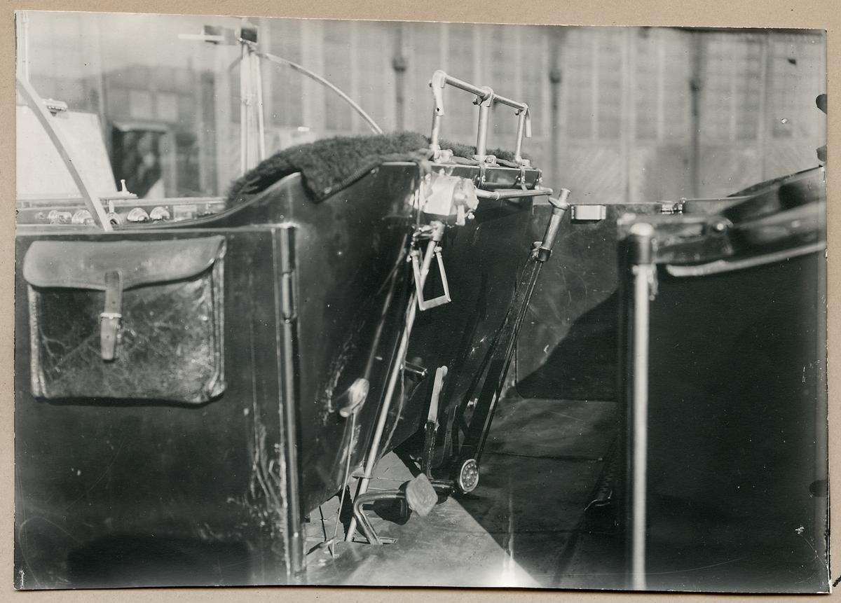 Motordressin förarplats. Fotot taget från sidan. Gas och broms pedal, samt handbroms och växelspak.