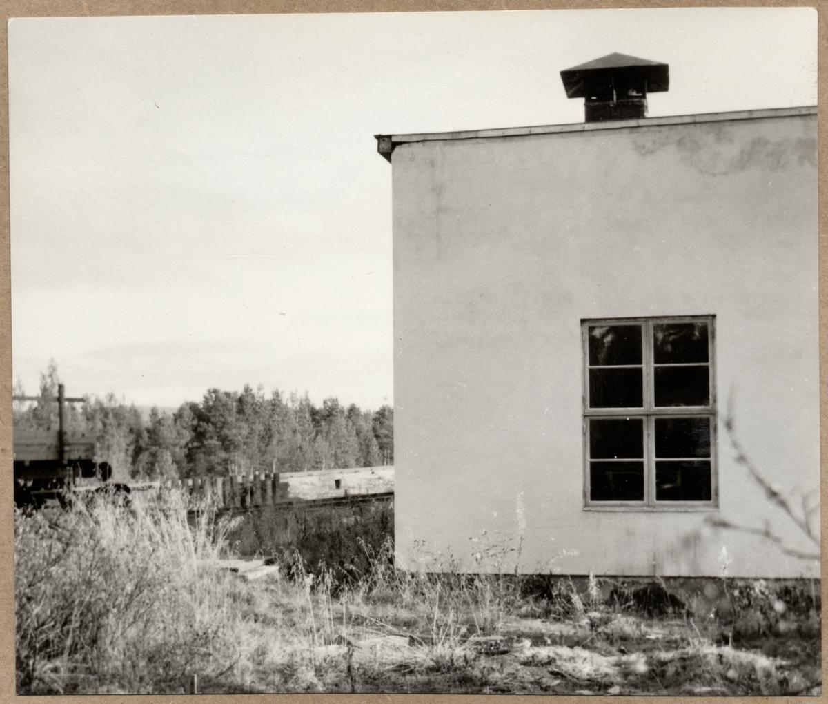 Bild av byggnad i Jokkmokk med brädor i bakgrunden,