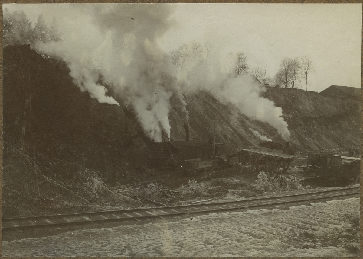 Dubbelspårsbyggnaden mellan Alingsås - Olskroken. Atlas Ånggrävmaskin SJ Q8  1005, tillverkad  1911. Torp grusgrop. Grävmaskin i arbete. Flyttbart galler för utsortering av större sten direkt vid skoplastning i vagn. Sandtvättningsmaskin.