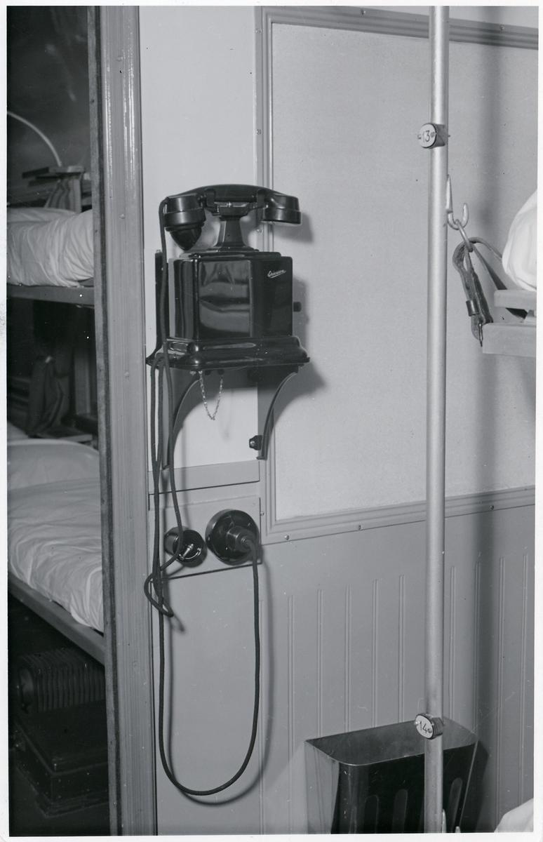 """Interiör från utställningståget  """"SJ i försvarets tjänst"""". Telefon i ambulansvagn."""