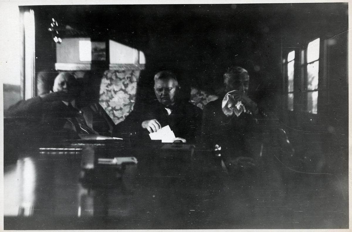 Tre män i en vagn.