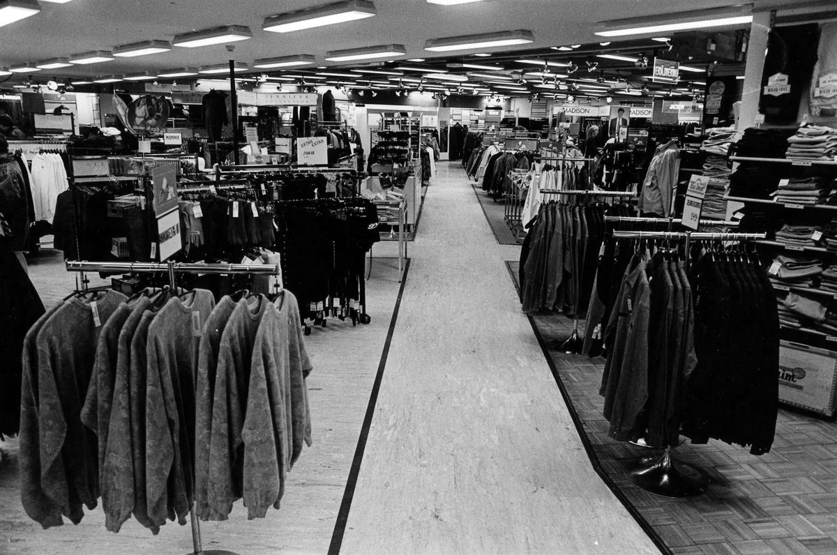 Foto taget på Gulins, kvarter Hjorten 19, där kläder står uppradade längs en mittgång. I november 1990 flyttade butiken tillsammans med Lindex in i EPAs gamla varuhus i kvarter Storken 12.