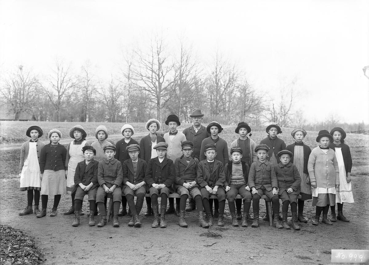 Kantor Bernhard Hultgren med skolklass intill Svinhults kyrkskola. Tiden är omkring 1913. Bernhard var upplysningsvis bror till fotografen.
