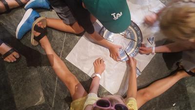 Barn som sitter på et gulv og setter sammen en knust keramikk tallerken