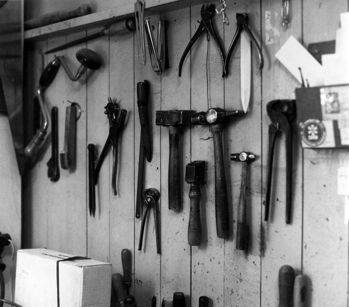 Bild på en vägg i bokbindarverkstaden. På väggen hänger diverse bokbindarverktyg. Åke Georgson (f 1910) började som bokbindare i kvarteret Gustaf 1 1932. Flyttade då fastigheten revs 1967 till en lokal vid Torggatan 7. Verksamheten nedlades i september 1982.