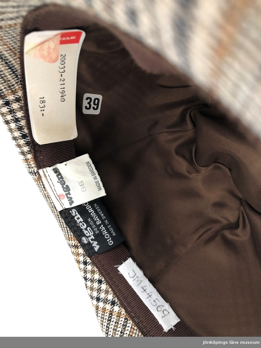 """Vitt- och brunrutig tyghatt till dam i herrhatts-modell. Kullen är sydd i sex kilar. Helstickat brätte. Monterad med ripsband och skinnimitation snott om varandra som avslutas med en knapp. Foder av brunt nylontyg. Foderband av brunt ripsband. Isydda etiketter: """"wigéns DESIGN GLORIA BAYARDÓ MADE IN SWEDEN"""", och """"wigéns 56 MADE IN SWEDEN"""", samt pappersetikett: """"wigéns 20033-211940 183:-"""". Inuti hatten sitter även en klisteretikett märkt: """"39""""."""
