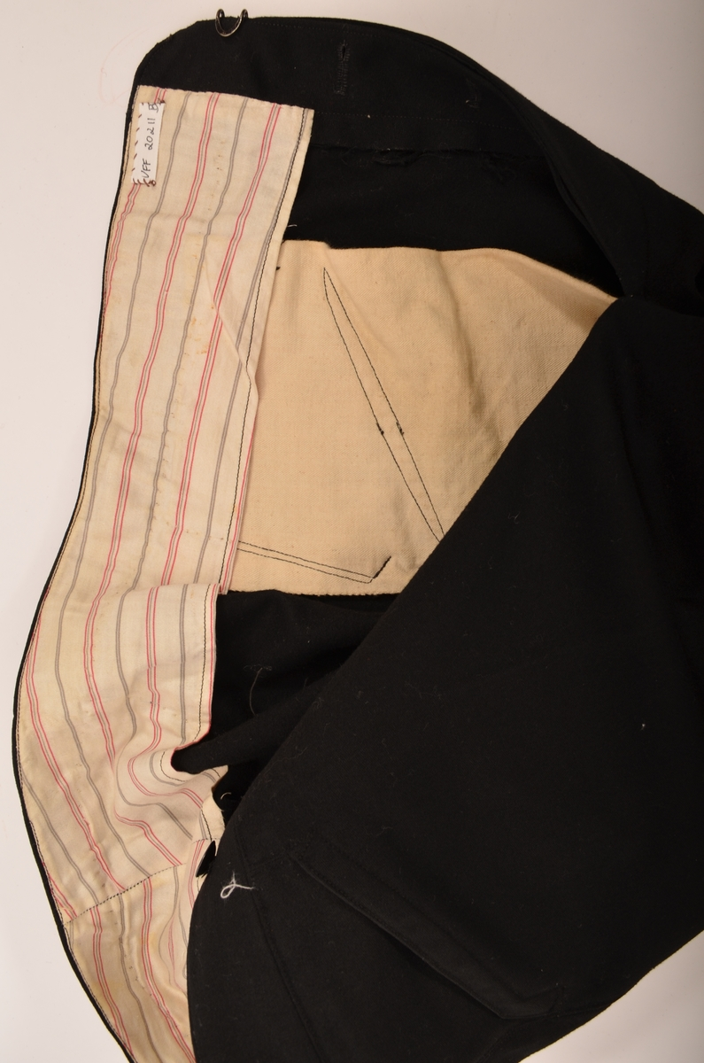Dress i svart klede. A. Jakke, B bukse, C vest.  Jakka har slag og krage, tre knappehol og tre knappar. Ei lomme på kvar side med klaff, og ei brystlomme på vestre side. Skuldersaumane er bakovertrekte. Bak ein svinga sidesaum på kvar side.  Buksa har linning  og gylf med knapping. To skrå lommer og spensel i sidene.  Vesten er fóra med stripa bomullstøy.  Fire knappehol og fire knappar. Ei stikklomme på kvar side og ei brystlomme. på venstre side. Det er også ei lomme på innsida.