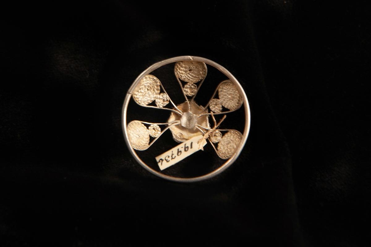 """En malja av silver. Filigranarbete i form av fem """"tungor"""" upp mot blomma i filigran.Stämplad på rundelns kant. JM.19973:a-e hör ihop."""