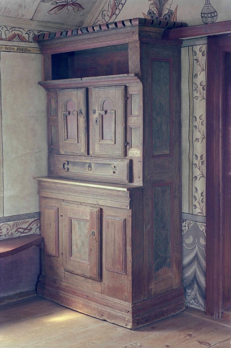 Skåp av furu, marmorerat i brunt, rikt profilerat med lister och speglar i blått och grönt. Rakt krön med utskuren dekor i olika färger, öppen del direkt under krönet, där efter ett dörrpar samt låda med skuren dekor. Underskåpet med en dörr, bred profilerad fotlist. Runda dragbeslag av metall, säkerligen sekundära.