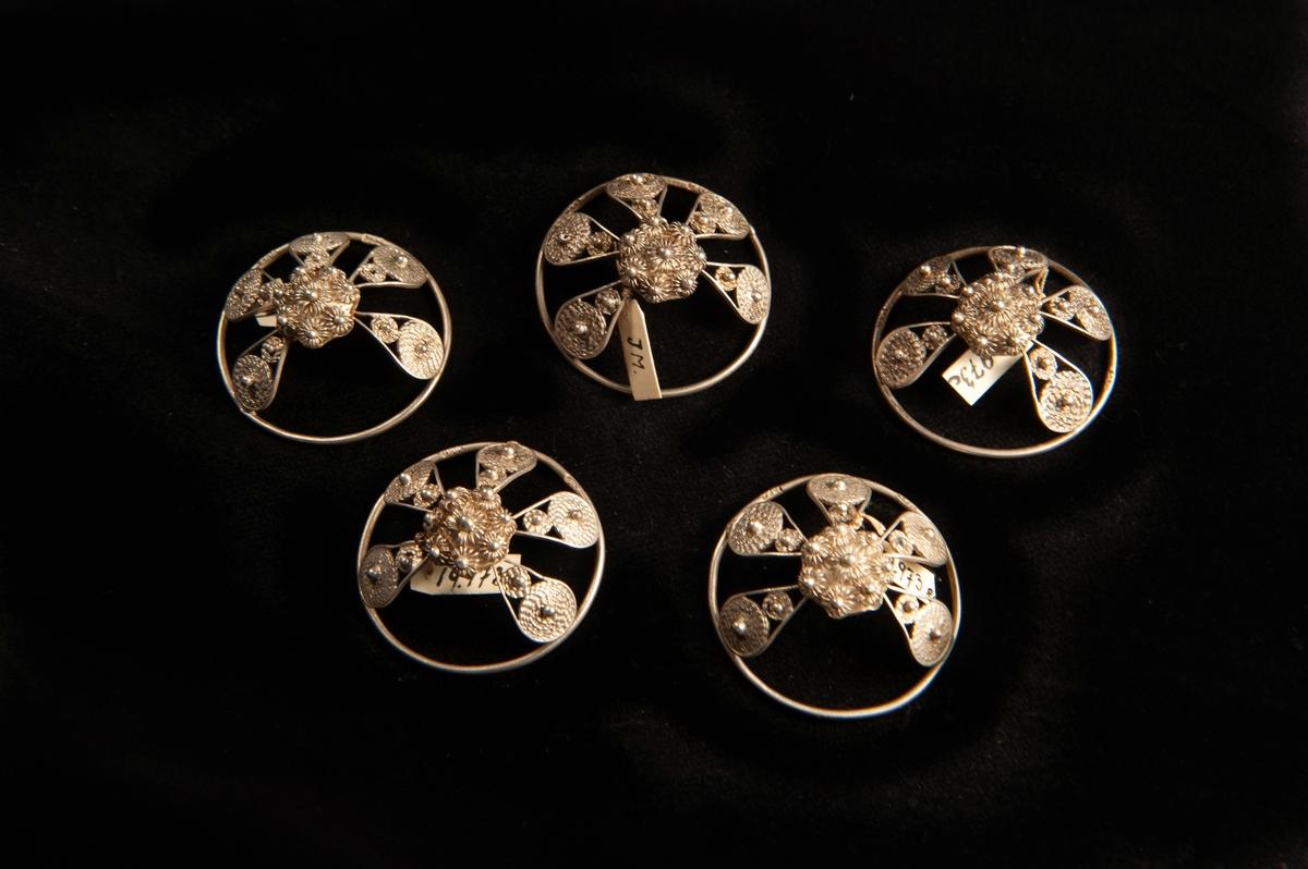 """En malja av silver. Filigranarbete i form av fem st.""""tungor"""" upp mot blomma i filigran. Stämplad på rundelns kant. JM.19973:a-e hör ihop."""