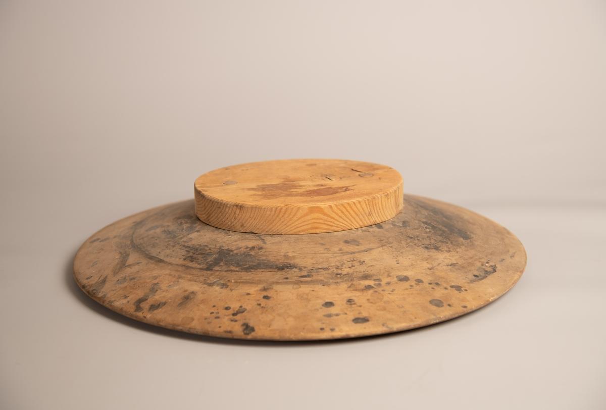 Oval bremblokk med flat topp og nedskrående kanter. På toppen er det to hull der man kan sette fast en hatteblokk for et hattehode. Følger med tilhørende oval, flat blokk med to trenagler som passer til. Litt flekkete på over og undersiden, men er generelt i god stand.  Stor blokk: A Liten blokk: B.