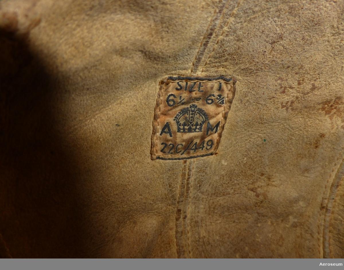 """En brittisk flygarhuva från andra världskriget (Type C Leather flying helmet). Huvan är välanvänd med spår av påverkan från mänskligt fett och svett. Det finns en del brukslitage på insidan, men lädret på utsidan känns dock fortfarande tämlingen väl infettat.  På insidan finns det en ettikett där det står: """"Size I 6½ to 6¾ A [krona] M [Air Ministry] 22C/449"""""""