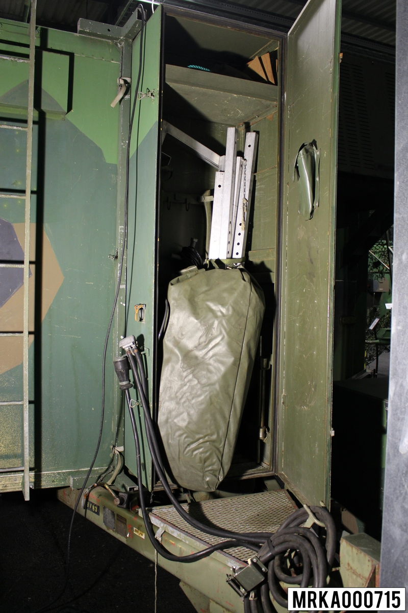 I det låsbara materielskåpet förvaras bl a bränsledunk för transportvärmare, domkraft, ljussluss, jordledningsspett med kabel, grävspade, huggyxa, varningstriangel, fälgnyckel och verktygsväska.