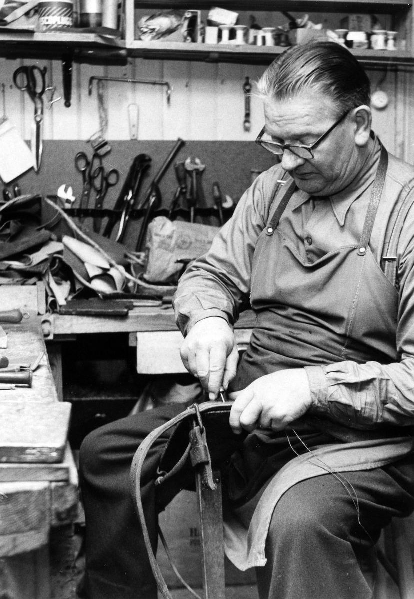 Sadelmakare Hallgren sitter på en stol omgiven av sadelmakarverktyg och arbetar på en sadel. Sadelmakeriet var beläget på Kungsgatan i kvarteret Duvan.