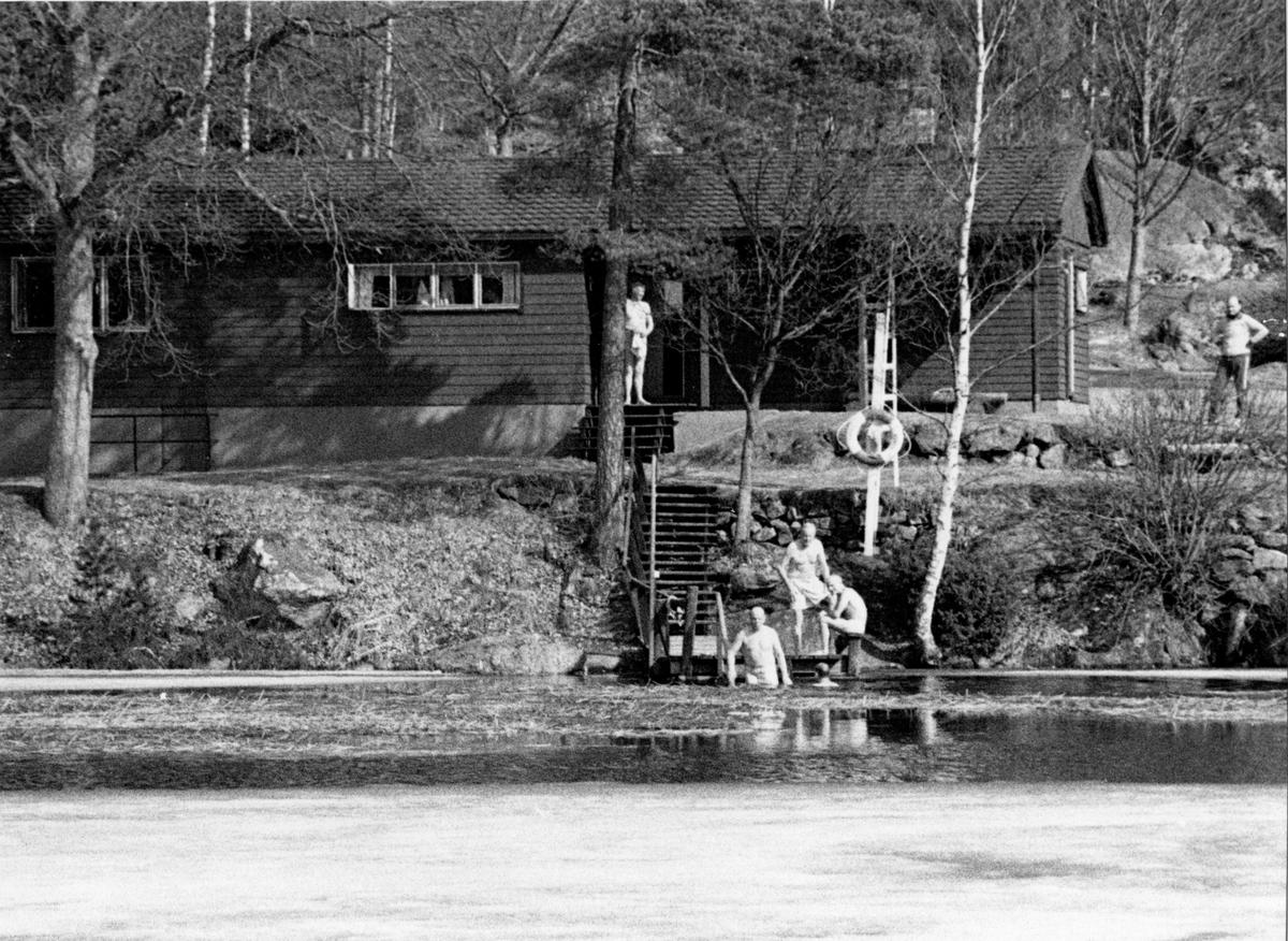 Friluftsklubbens stuga i Ängabo där tre män syns vid bryggan och två män står uppe vid stugan.