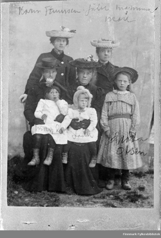 Gruppebilde av fire kvinner og tre barn, oppgitt til å være tatt i Skjøtningberg. Kvinnene har datidens moteriktige stråhatter med utstoppede fugler, frukt og blomsterpynt og sorte lange kåper/kjoler. Det står navn skrevet på bildene. Det kan se ut som det står Magda (f. 1902) og Laila (f. 1903) Lund på de to små jentene i hvite kjoler. Jenta til høyre har etternavn Olsen. Over kvinnene med hatt står det muligens Karin Hanssen (?), Julie, mamma og muligens mor eller Mari(e)? . En informant har gitt en opplysning: En av damene er muligens Karen Martha Stenersen (f. 1883 i Kifjord), hun var barnepike i Skjøtningberg rundt 1900. Hun ble gift Leiknes. Fotografens navn starter på Ei... Bildet er avfotografert og vår original er et negativ av reprobildet. Bildeserien FBib.18017-001-018 har tilhørt Gerd Lund Barbala fra Friarfjord. I notatene står det at bildet er fra Skjøtningberg. Bildet ser ut til å være fotografert utendørs, det er gress og grus på bakken og det er hengt opp en tøybakgrunn bak kvinnene, muligens på en husvegg. Den minste jenta til venstre ser ut til å ha noe som ligner en samisk stjernelue på hodet, mens jenta til høyre har kyse i pels. Damene som holder barna har hansker på hendene.