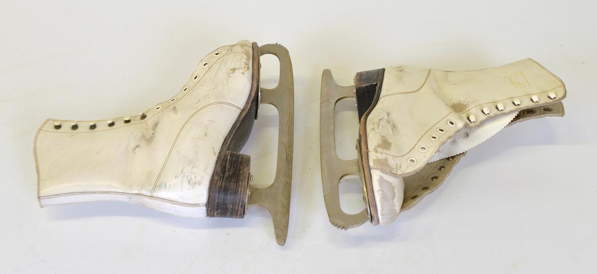 Skridskor av vitt läder, snörning över fot och vrist. Kraftig lädersula och -klack, Stålskena med spetsnaggning. Storlek 35  Tillvaratagna på vinden i Palladiumhuset, Alingsås  Modell: Piruett