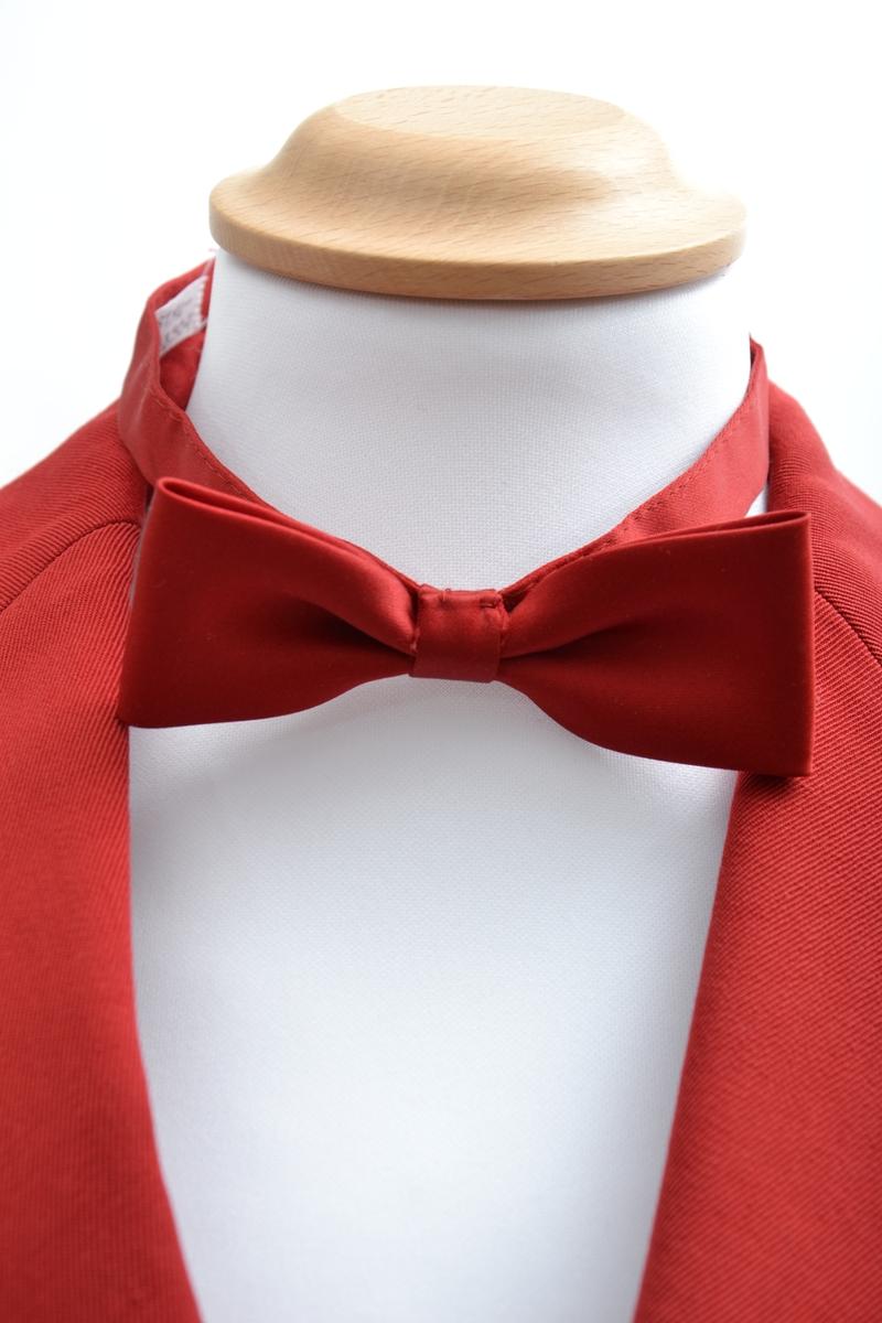 Korpsuniform bestående av jakke, skjorte, sløyfe,to bukser, hansker og lue. Jakken er dobbeltspent med 4 metallknapper, skulderklaffer, hvit snor fra skulderklaff til brystlomme og et felt med et smalt hvitt bånd på armene. Buksene er lys grå med hvit stripe i siden. Enkel hvit skjorte med rød sløyfe til. Uniformsluen er rød med hvite bånd og dusk i pannen. Et par hvite bomullshansker hører til. Jakken er i størrelse 10 år.