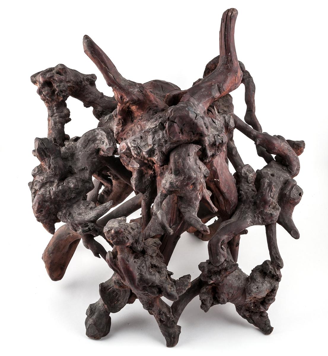 Kinesisk skulptur av trä.  Grenar monterade samman. Drakhuvud täljt i en av träbitarna.