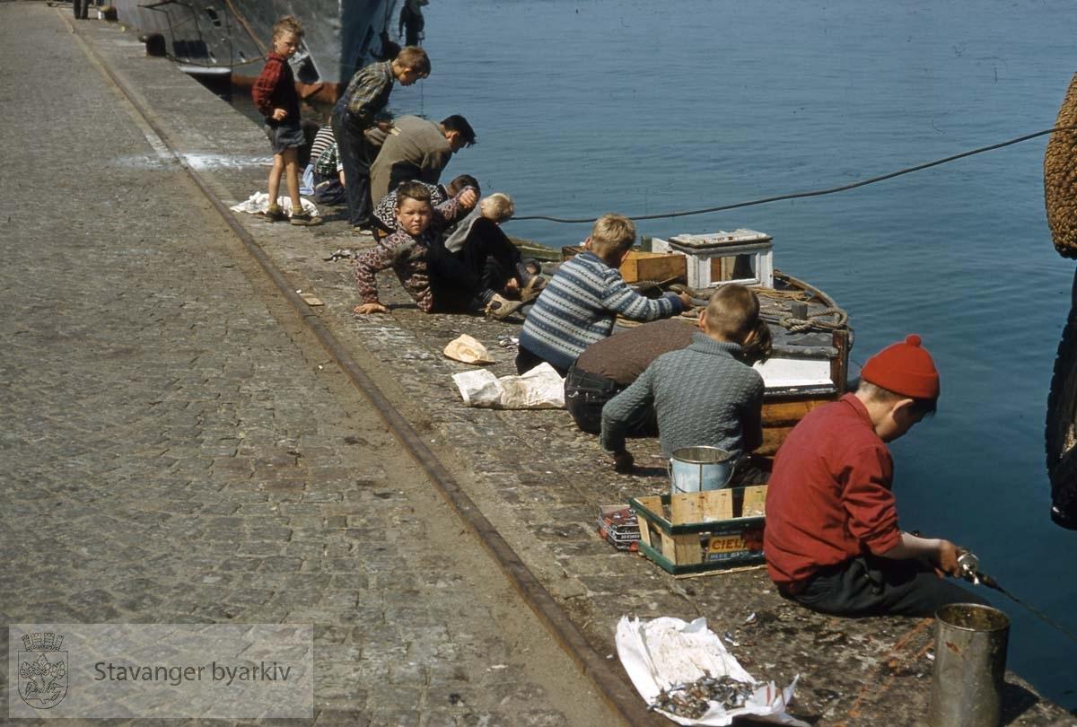 Gutter som fisker på kaien