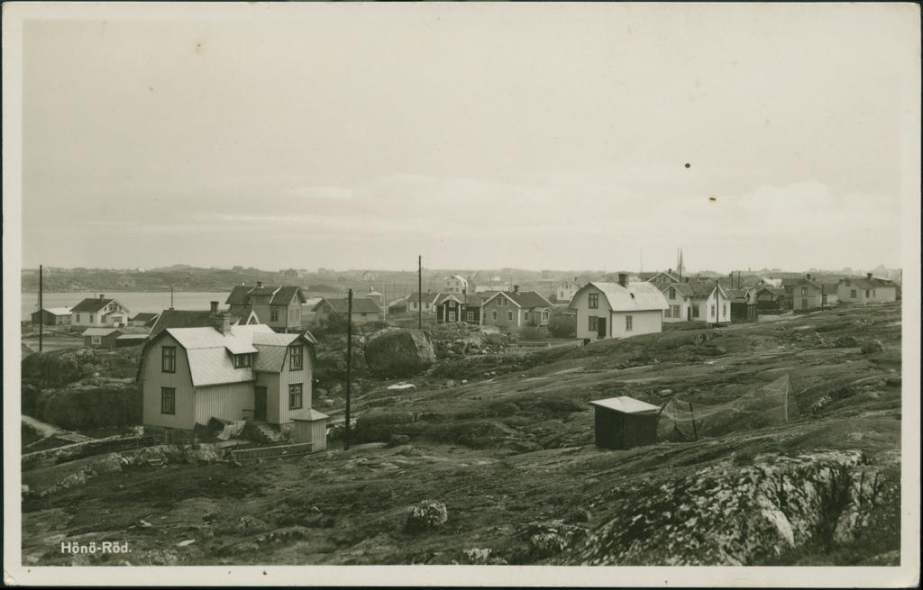 Vykort med motiv över Hönö-Röd med bebyggelse, till vänster i bild ligger en havsvik, i bakgrunden syns ett kyrktorn.