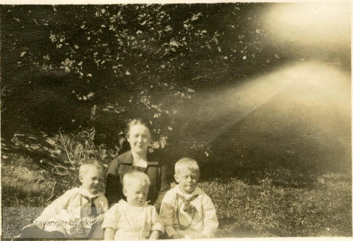 Mor og tre barn i hage