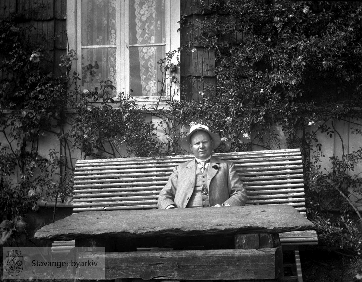 Birger Pedersen på benk utenfor huset.