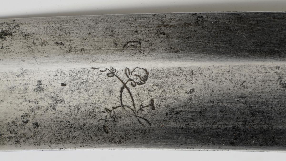 Tyrkisk krumsabel med helstøpt messingfeste som ender i nedbøyd krøll øverst. Fremre parerstang er brukket. Rett bakre parerstang ender i en bllomsterknopp. Grepet har støpt dekor med dobbel blomsterranke og bladdekor..På utsiden en oval med en hane/høne med en fot på et egg/ en sten. Grepet har noen tyrkiske skifttegn på undersiden tilsammen tre ord. Er ord er navnet Jamal, som kan være eier av sabelen eller smeden. Krum enegget klinge med kileformet tverrsnitt og merker i form av blomster. Balg i svart lær med messing beslag m. to bæreringer, bladdekor og mann-i-halvmåne.