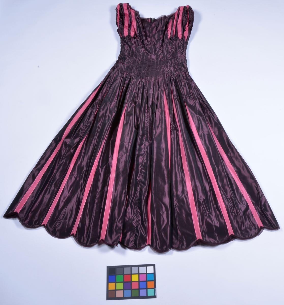 Av randigt taftsiden i färgerna lila och rosa. Modellen helskuren, midjepartiet har insydda  veck som döljer de rosa ränderna. Livet och kjolen har löst liggande veck där randningen  framträder, korta ärmar.  Klänningen är sydd 1937 och modellen ritad av Jonas Alströmer.