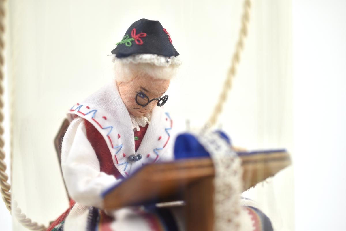 Landskapsdocka i cellofanask. Dockan, klädd i den kvinnliga Skedevidräkten från Östergötland, sitter på en stol med en knyppeldyna framför sig.