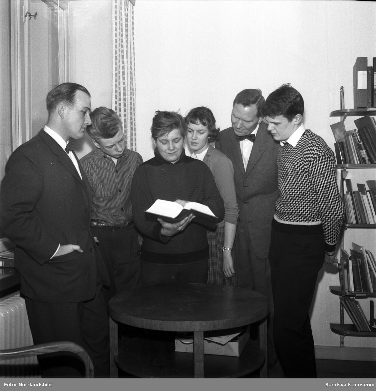Några elever och lärare i en skola i Timrå bläddrar i en tjock bok.